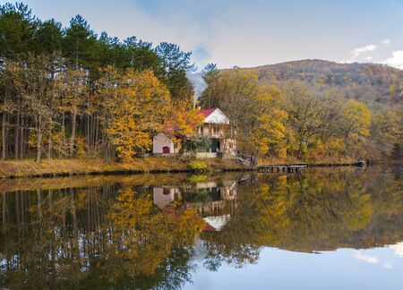 Lake with chalet and autumn woods on the shore