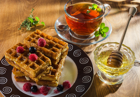 tea and freshly baked wafers with berries and honey