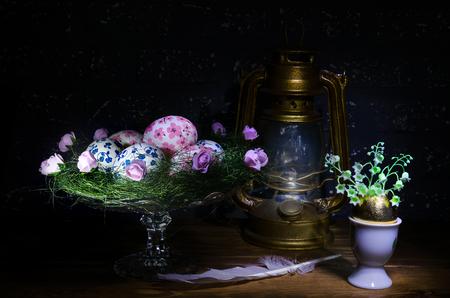 easter eggs and kerosene lamp on wooden table in dark Stock Photo