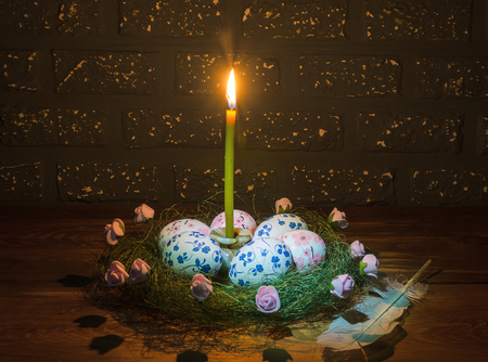 Easter eggs and candle on wooden table in dark