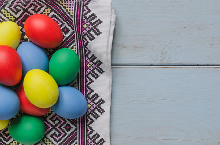Easter eggs on dishcloth with ornament on white wooden table