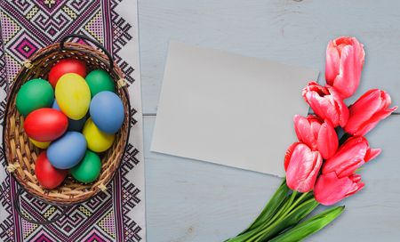 Easter eggs in basket and blank card with tulips Stock Photo