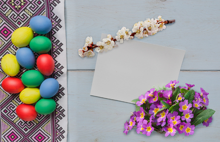 Easter eggs on dishcloth with ornament and blank card with flowers Stock Photo