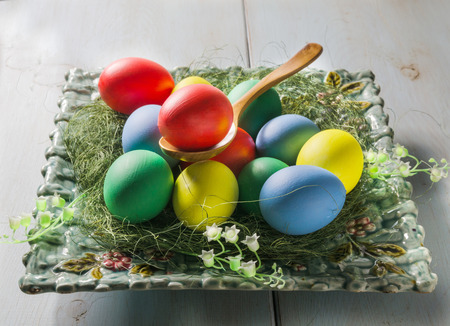 Easter eggs with spoon in a plate on white wooden table