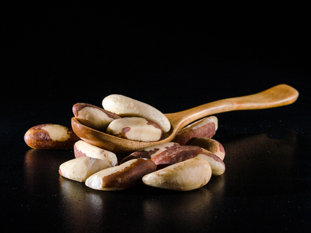 seeds of brazil nuts in spoon in darck