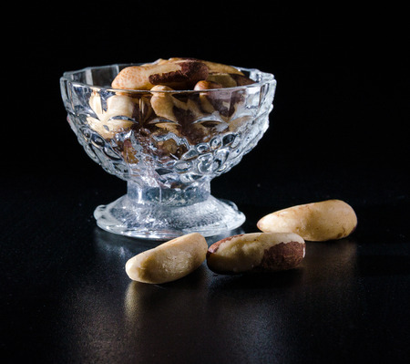 seeds of brazil nuts in glass bowl in darck