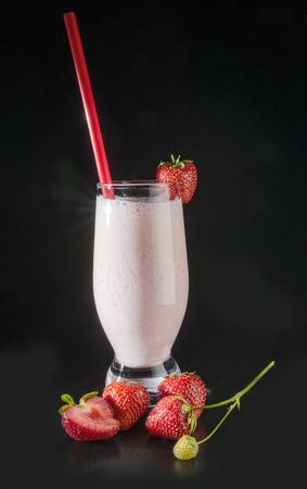 Glass with strawberry smoothie in dark