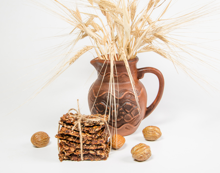 homemade crackers with ears in ceramic jug on white background
