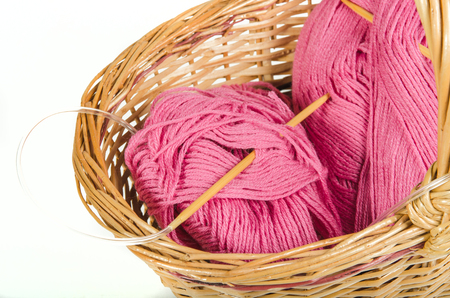 skeins of pink yarn and bamboo knitting needles in a wicker basket