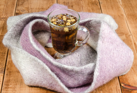 knitted scarf and cup of hot tea on wooden table