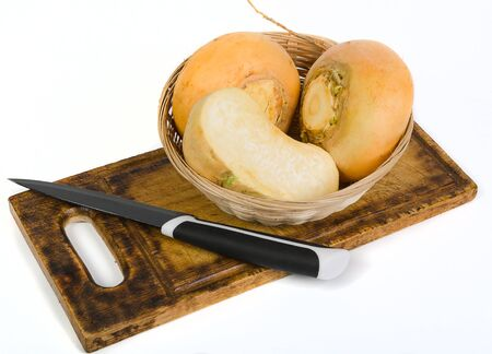 Round yellow turnip and a knife on a cutting board on white