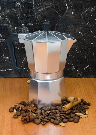 Silver geyser coffee maker with beans and spices on table