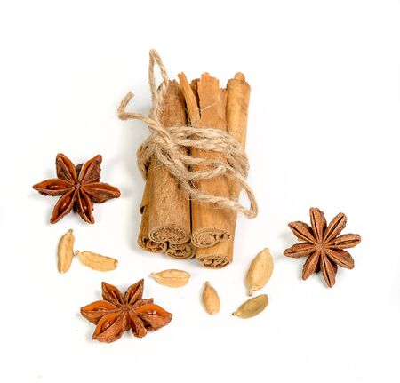 bunch of cinnamon sticks with cardamom and star anise on white background Reklamní fotografie