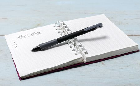 """Open notebook on wooden table with pencil. The inscription in the notebook """"Next steps"""""""