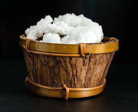 white crystals of salt on a black background in dark