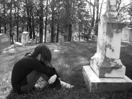 A grieving girl mourns in a graveyard, curled up in front of a large grave.
