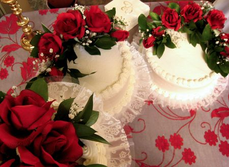 A shot of three beautifully decorated wedding cakes with red roses.