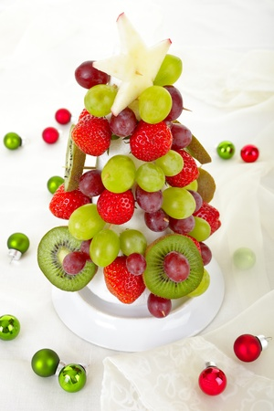 Fruit Christmas Tree, cone, black grapes, kiwis and strawberries Banque d'images