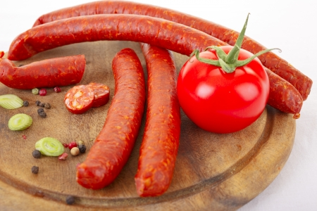 cutting bord: Spicy sausages and fresh tomato on wooden cutting bord