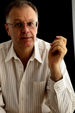 Mature man talking on black background Stock Photo - 15177305