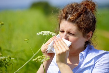 Woman with a flu or an allergy sneezing into her handkerchief in spring Imagens - 15500486