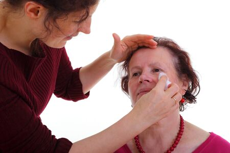 ceremonial make up: Young woman cleaning face of senior woman  Stock Photo