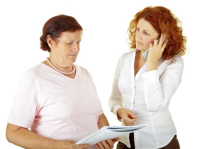 senior woman and young woman holding a paper photo
