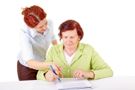 young woman helping senior woman to write a letter  photo