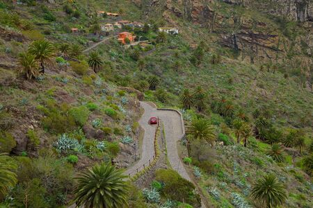 Mountain winding road with a red car photo