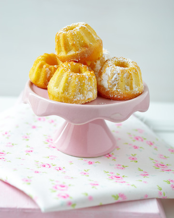 Sweet bundt cakes on a pink cake stand Stock Photo