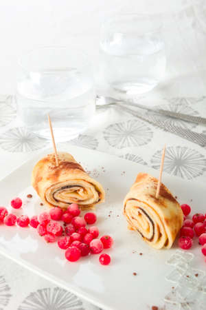 Rolled crepes with red currant.