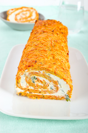 Homemade carrot roll with cream cheese and herbs.