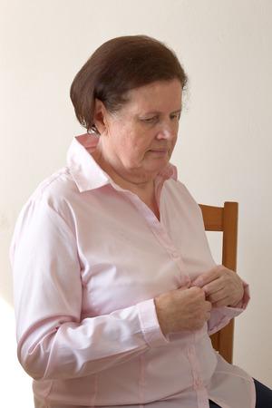 blusa: Mujer mayor abotonarse la blusa.