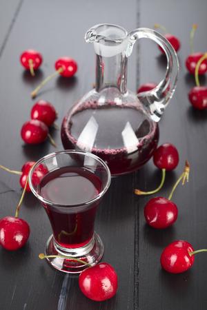 liqueurs: Cherry liqueur in a glass and fresh fruit.