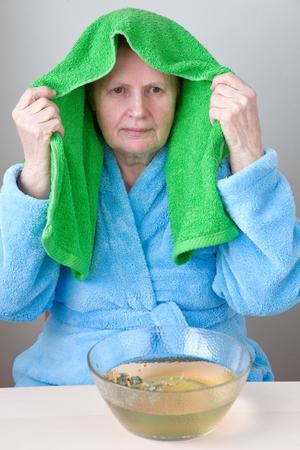 Elderly woman inhaling over a bowl