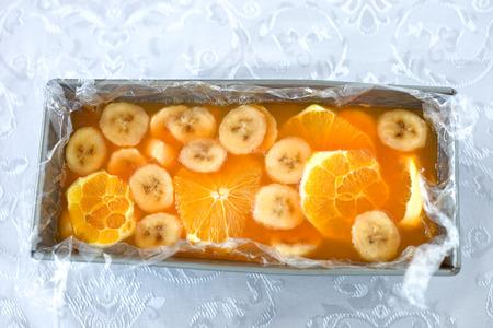 Orange banana gelatin dessert in a baking form