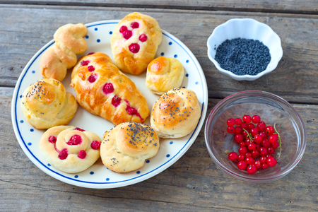 Sweet yeast rolls with red currant and poppy seeds.