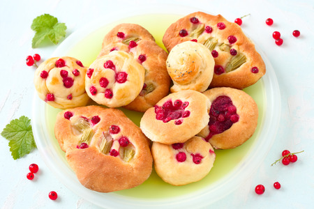 Sweet yeast rolls with  red berries and rhubarb