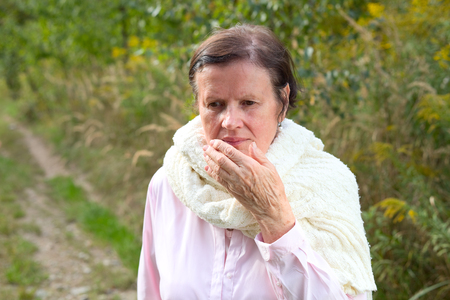 Portrait of elderly woman coughing outdoors. Cough.