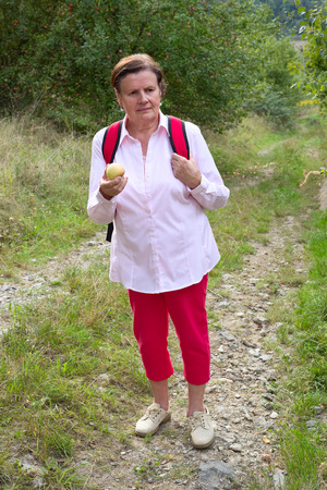 Senior tourist hiker with an apple Banque d'images