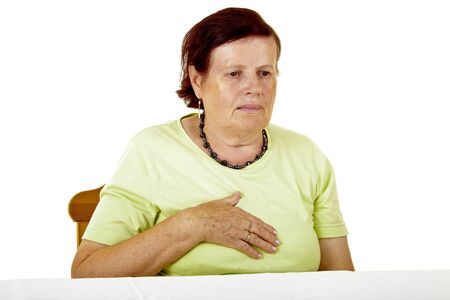 Senior woman feeling heart pain and holding her chest.