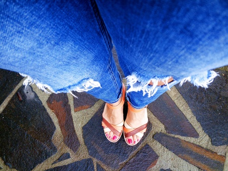 jeans: Female legs and feet with ripped jeans and sandals Stock Photo