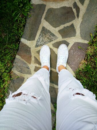 pants: Point of view with woman legs and feet wearing white ripped jeans and sneakers outdoor
