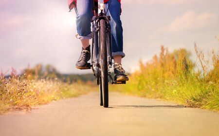 A woman is riding a bike through nature