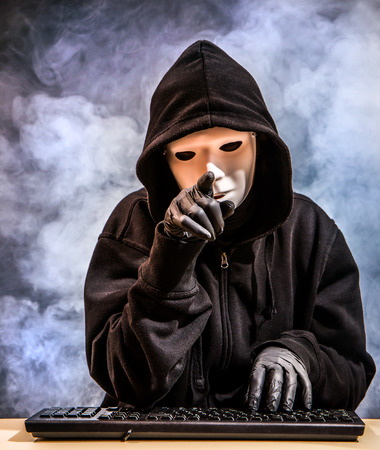 A hacker sits in front of the keyboard of a computer