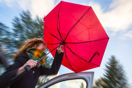 A woman tries to open her umbrella in a strong wind Stok Fotoğraf