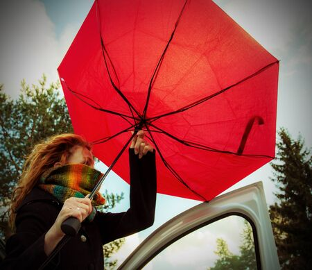 A woman tries to open her umbrella in a strong wind Stock Photo