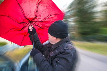 A man gets out of his car and tries to clamp his umbrella Stok Fotoğraf