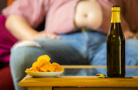 A fat man sitting on a sofa, eating potato chips and drinking beer