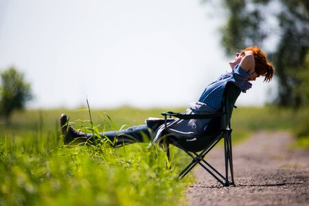 A woman sitting on a chair on a green meadow